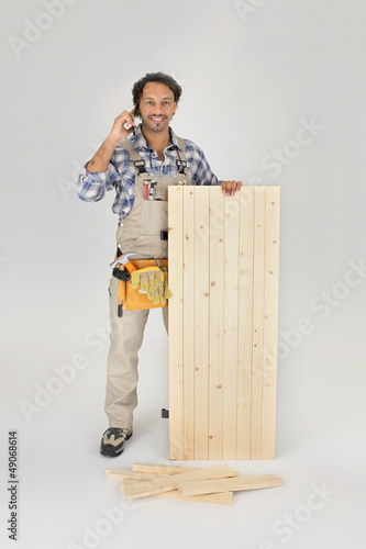 Carpenter stood with wooden door