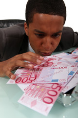 avid businessman looking at the banknotes on his desk