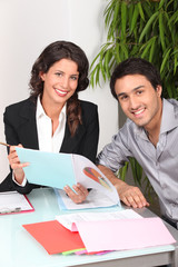 Two cheerful workers looking at financial information