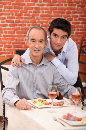 Father and son eating together in restaurant