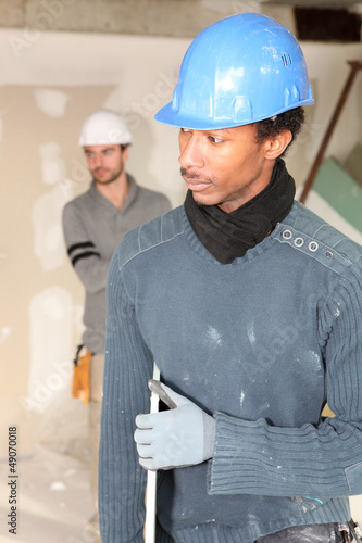 Two men carrying plaster board