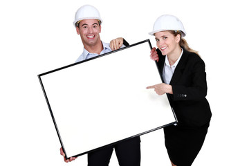Cheerful architects with a blank board