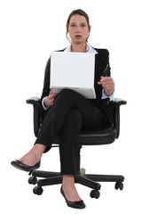 surprised businesswoman sitting in a chair and holding laptop