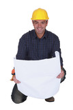 Smiling tradesman looking at a blueprint