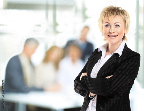 confident business woman with team behind