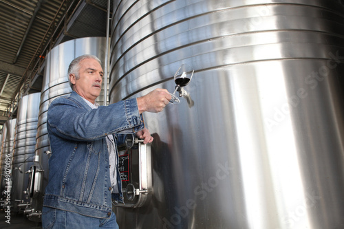 Winemaker with a glass of wine in the cellar