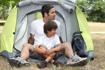 Father and son sitting outside a tent