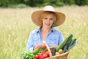 Woman with basket of vegetables walking through a field