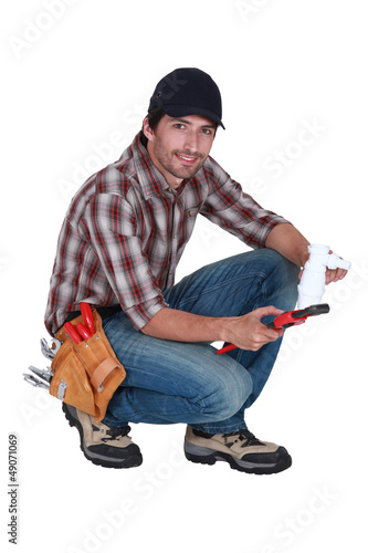 plumber holding a plastic pipe and a spanner