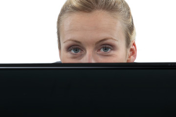 Woman hiding behind laptop computer