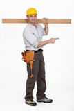 carpenter carrying plank over his shoulder