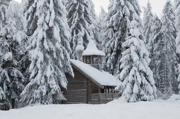 Деревянная часовня в снежном лесу. Зима, север