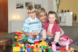 happy grandmother playing legos with grandchildren poster
