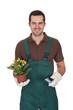 Happy young gardener holding flowers