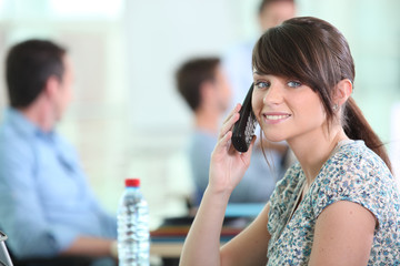 Woman with mobile phone colleagues sat in background