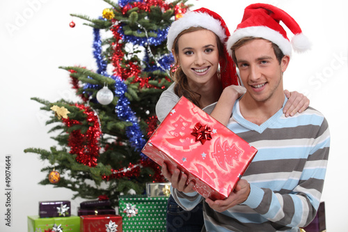 Couple wearing festive hats stood by Christmas tree