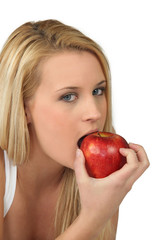 Blond woman eating red apple