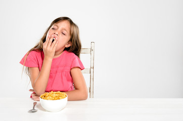 Tired sleepy young child with bowl of breakfast cereal