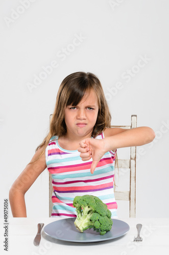 Frowning girl with her broccoli vegetable show thumbs down