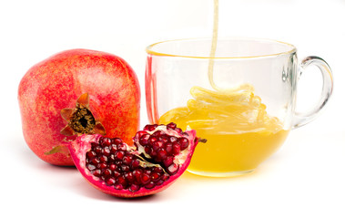 pomegranate and honey in a cup of  glass on white