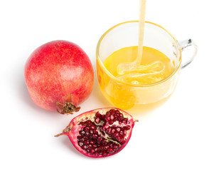 pomegranate and honey flowing in a cup of  glass on white