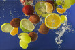 Fruits splash in water with bubbles against blue background