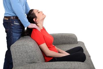 Man massaging woman on a sofa