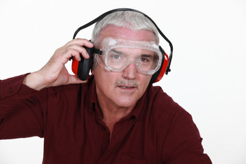 Man in safety goggles and ear defenders