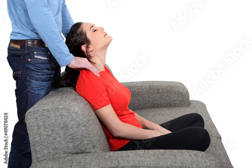Man massaging woman on a sofa