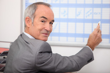 Grey haired man writing on calendar