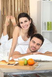 Couple with breakfast served on tray