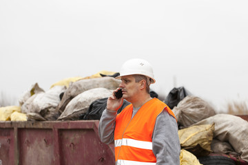 Worker with cell phone near garbage and container