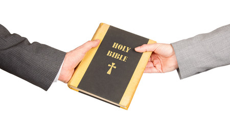 Man and woman in business suits are holding a holy bible