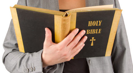 Woman in business suit is reading a holy bible
