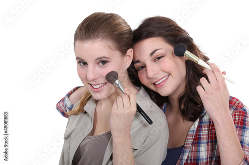 Two women applying make-up