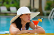 girl with a cocktail at the edge of the swimming pool