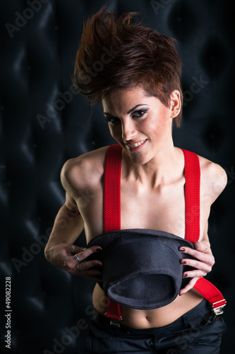 Crazy girl with red suspenders holding a hat