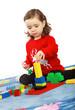 Ein Mädchen baut einen Turm mit Legosteinen