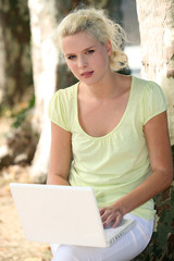 Blond girl in park with laptop