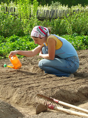 woman sowing seeds and watering