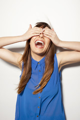 Close up of a happy young woman covering her eyes