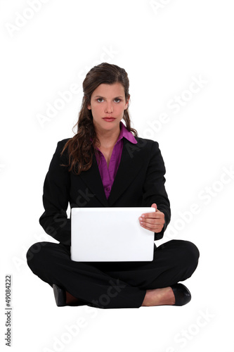 Brunette businesswoman sat cross-legged on the floor