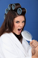Woman with hair curlers singing in a brush