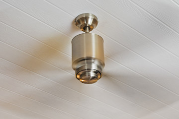 Ceiling fan on white wood panelling