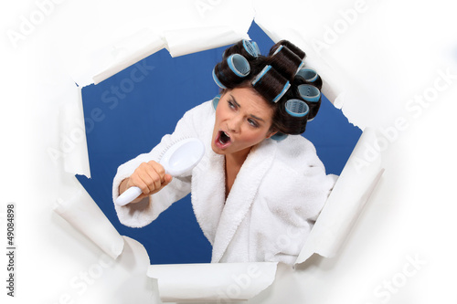 Woman wearing hair rollers, singing into brush