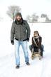 Lachendes Paar mit Holzrodel