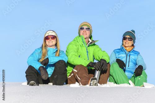 Skisportler sitzen im Schnee