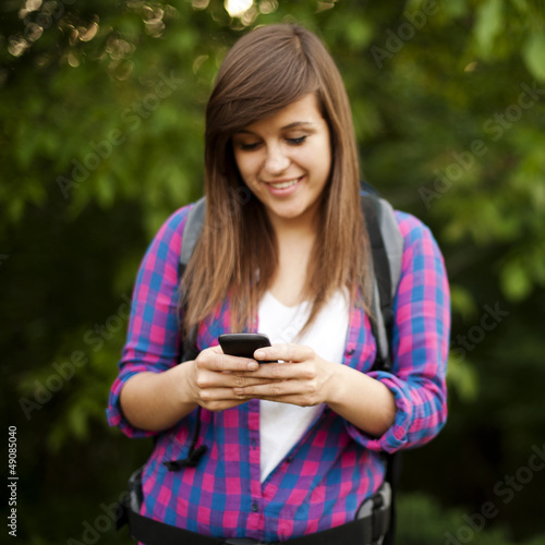 Beautiful female hiker texting