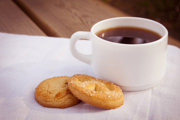 Cup of coffee with cookies on cloth and wooden table.