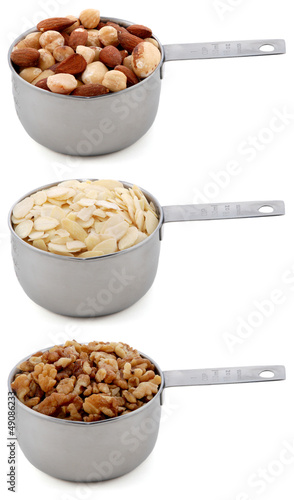 Whole nuts, flaked almonds and chopped walnuts in cup measures